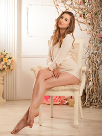 Silky skinned Ginger Frost is sitting serenely in her cream dress 00