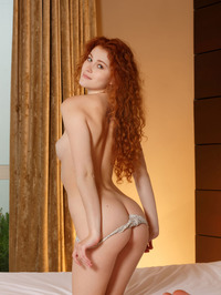 Gorgeous redhead Adel C is on her bed 01