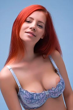 Big boobed redhead posing naked in a studio